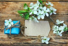 Blue gift box, blank paper tag and branch plum. Blue gift box, blank paper tag and branch of a flowering plum on a wooden table Royalty Free Stock Images
