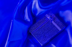 Blue gift box with blue ribbon bow on blue satin textile Royalty Free Stock Images