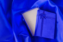 Blue gift box with blue ribbon bow on blue satin textile Royalty Free Stock Photo
