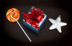 Blue gift box, candycane and white christmas star on black Royalty Free Stock Image