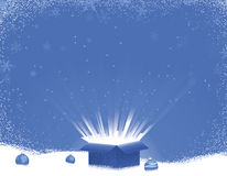 Blue Gift Box Explosion Winter Scene. Decorative blue gift box with lights rays bursting out. Snowy background with faint snowflake designs Royalty Free Stock Image