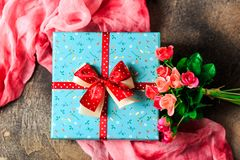 Blue gift box with flowers and red ribbon with rose flowers on brown table woman day stock photography