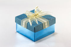 Blue gift box with gold ribbon and bow Stock Images