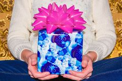 Blue gift box in hand for important day on white wool background.  Royalty Free Stock Images