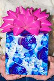Blue gift box in hand for important day on white wool background.  Stock Image