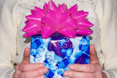 Blue gift box in hand for important day on white wool background.  Stock Photos