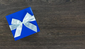 Blue gift box with light blue bow on wooden background Stock Photos