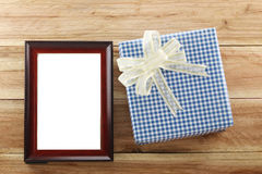 Blue gift box place near Brown wooden frame on the wood floor. Blue gift box place near Brown wooden frame on the wood floor in concept of Christmas and New Stock Image