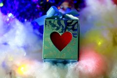 Blue gift box with red heart  on soft snowy  background. Royalty Free Stock Images