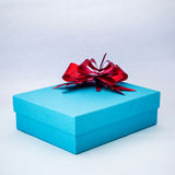 Blue gift box with red ribbon on isolated white Stock Photography