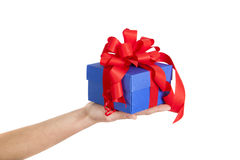 Blue gift box with red ribbon in woman hand. Isolated stock photography