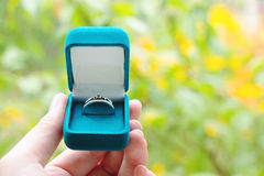 Blue gift box with ring in hand on background of greenery. Selective focus, toned image, film effect, macro, close-up. Blue gift box with ring on background of Royalty Free Stock Photography