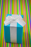 Blue gift box on striped colored background Stock Images