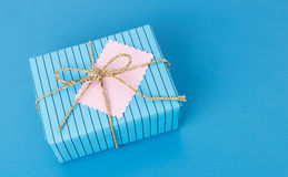 Blue gift box with tag on colorful background Royalty Free Stock Photography