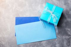 Blue gift box and two envelops on concrete background. Blue gift box and two envelops on the concrete background Royalty Free Stock Image