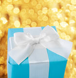Blue gift box with white bow on background of golden lights Stock Image