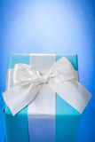 Blue gift box with white bow on bluee background with copyspace Stock Photography
