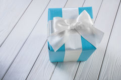 Blue gift box with white bow on white wooden boards Stock Images