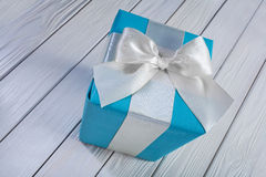 Blue gift box with white bow on white wooden table Royalty Free Stock Photography