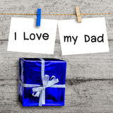 Blue gift box on wooden wall with a blank paper Royalty Free Stock Photo