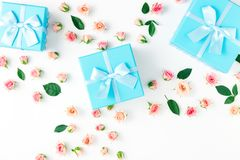 Blue gift boxes collection with pink roses on white background. Blue gift boxes collection with pink roses on a white background in flat lay style. Top view Royalty Free Stock Images