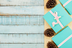 Blue gift boxes with pink ribbons and fircones on wood Stock Photos