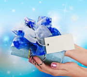 Blue gift in a female hand Stock Photos