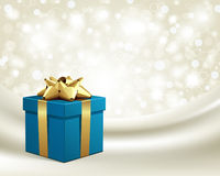 Blue gift with gold bow on silk Royalty Free Stock Photography