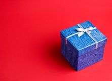 Blue gift on a red Royalty Free Stock Image