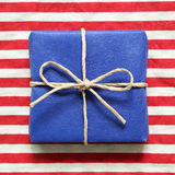 Blue gift on red striped background. Blue gift on red striped cloth background Stock Images