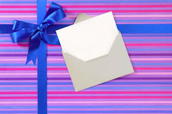 Blue gift ribbon bow on candy stripe wrapping paper, blank Christmas card, copy space Stock Images