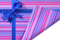 Blue gift ribbon bow on candy stripe wrapping paper, corner folded open revealing white copy space inside Stock Photo