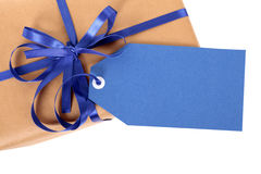 Blue gift tag or label on brown paper parcel or package, top view, close up Royalty Free Stock Images