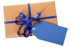 Blue gift tag or label on brown paper wrapped parcel, isolated on white, top view Royalty Free Stock Photography