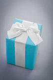 Blue giftbox on gray background Royalty Free Stock Image