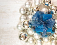 Blue giftbox surrounded by silver baubles Stock Photography