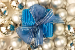 Blue giftbox surrounded by silver baubles Royalty Free Stock Images