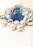 Blue giftbox surrounded by silver baubles Royalty Free Stock Photos