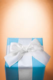 Blue giftbox with white bow on light brown background with copys Royalty Free Stock Photography