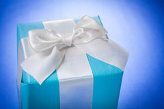 Blue giftbox with white ribbon on blue background Royalty Free Stock Image