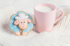 Blue gingerbread sheep with cup of milk on white knitted backgro Stock Photos