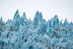 Close up view of the jagged blue ice of Holgate Glacier in Alaska`s Kenai Fjords National Park. Blue glacial ice craggy peaks against an overcast sky in the royalty free stock photos