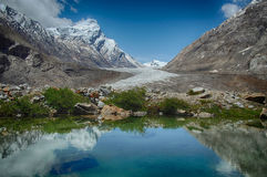 Blue glacial lake: in the mirror of water reflects bright sky with white clouds, green plants along the edge of the water and huge Royalty Free Stock Image