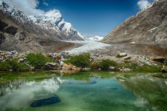 Blue glacial lake: in the mirror of water reflects bright sky with white clouds, green plants along edge of the water and huge mou Stock Image