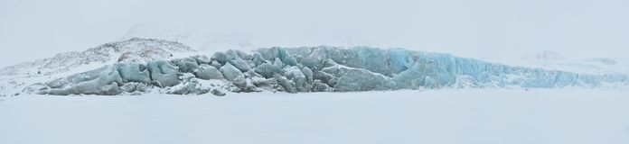 Blue glacier covered by snow. Cold snowy winter day, Greenland Stock Images