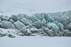 Blue glacier covered by snow. Cold snowy winter day, Greenland Stock Photo