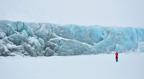 Blue glacier covered by snow and standing woman. Cold snowy winter day, Greenland Stock Image