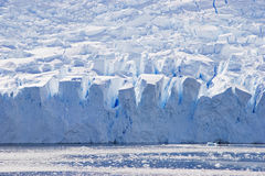 Blue glacier face in silhouette with big crevices. Massive face of a deep blue glacier with big chunks of ice Royalty Free Stock Photos