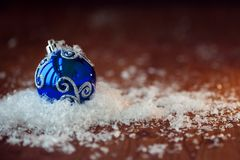 Blue glass ball. Christmas toy. In a pile of snow, wood textured background, rustic style Stock Images