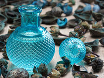 Blue glass bottle surrounded by dried plants. Close-up of filled blue glass bottle surrounded by dried plants on wooden surface. Cool fragrance concept Stock Photo